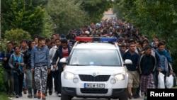 Мигранттарды бастап бара жатқан Австрия полициясы. (Көрнекі сурет).