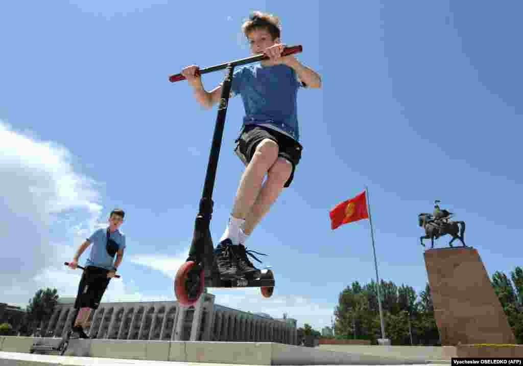 Kyrgyz boys ride scooters on International Children's Day in central Bishkek on June 1. (AFP/Vyacheslav Oseledko)