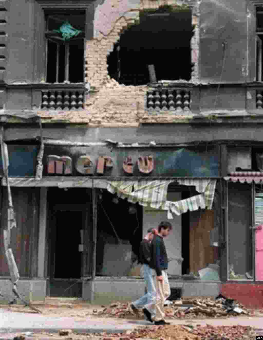 Two residents of Sarajevo walk past a destroyed building on Marshal Tito Avenue in June 1992 - The UN's International Criminal Tribunal for the former Yugoslavia has charged Karadzic with being responsible for his army's shelling of parts of Sarajevo and attacks on civilians during a 43-month siege of the city, during which thousands were killed or wounded.
