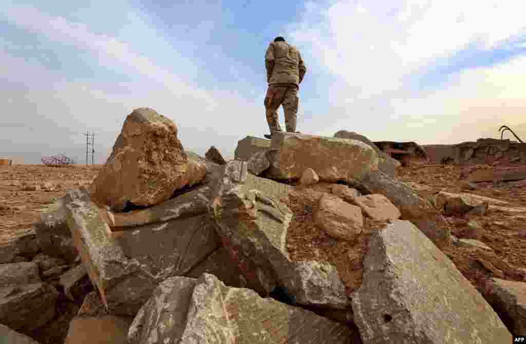 An Iraqi soldier stands on the ruins of an archaeological site