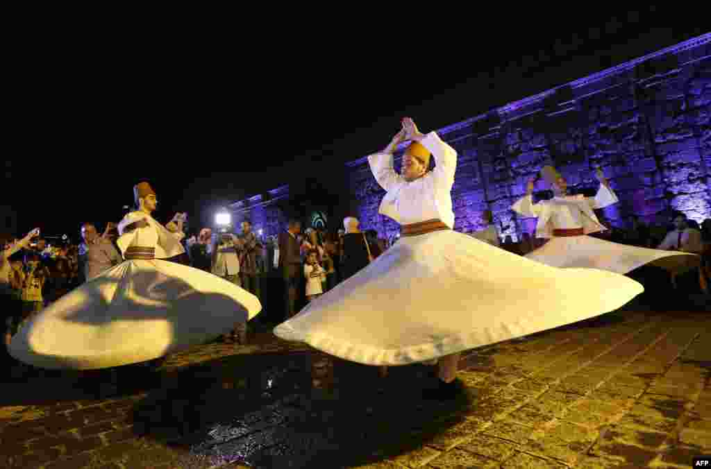 Syrian whirling dervishes perform in a celebration during the Muslim holy month of Ramadan outside the Umayyad Mosque in the old city of the capital, Damascus. (AFP/Louai Beshara)