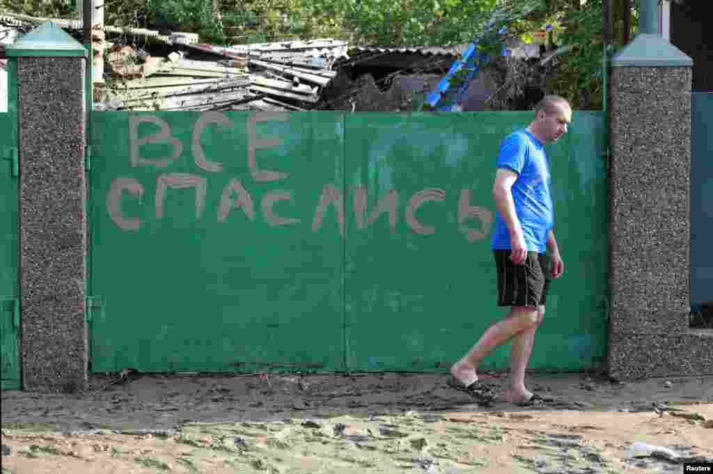 "A local resident walks in mud from the floods in the town of Krymsk past a sign reading  ""Everyone has escaped (found salvation)."""