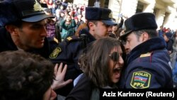 Police officers block activists during a rally held to support women's rights and to protest against violence toward women on International Women's Day in Baku on March 8.