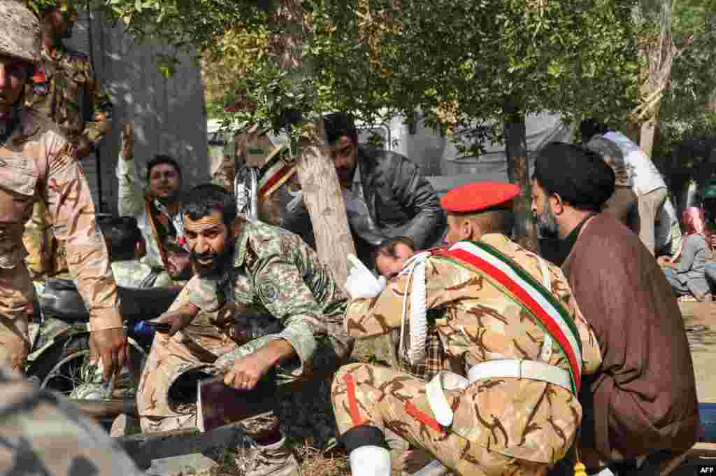 Soldiers and a Shi'ite Muslim cleric (right) sitting close to the ground seeking cover at the scene of the attack.