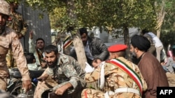This picture taken on September 22, 2018 in the southwestern Iranian city of Ahvaz shows soldiers and a Shiite Muslim cleric (R) sitting close to the ground seeking cover at the scene of an attack on a military parade.