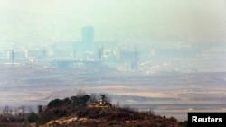 Вдалині, в імлі – комплекс Кесон на території Північної Кореї, попереду – північнокорейський прикордонний пост, фото з боку Південної Кореї 4 квітня 2013 року