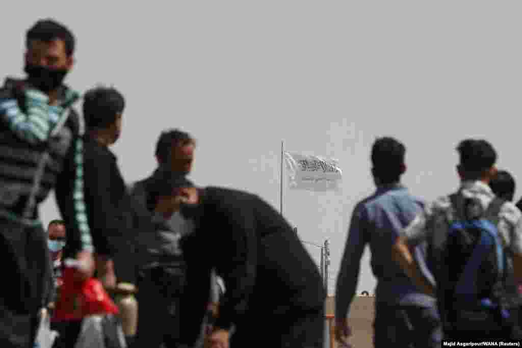 """Иранның """"Даукарун"""" шекара бекетіне қарама-қарсы беттегі Ауғанстан аумағында тәліптердің қара жазуы бар ақ туы желбіреп тұр."""