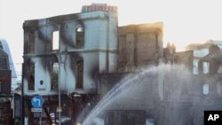 Firefighters douse a burned-out building following a week of violence on Britain's streets.