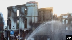 Firefighters douse a burnt out building following following a night of violence on the streets of London.