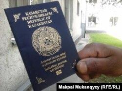 Негусса Тессема показывает свой документ, который выдают лицам без гражданства.