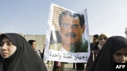 "Protesters hold a poster depicting a montage of two faces, Sunni legislator Dhafer al-Ani and Saddam Hussein, and reads below: ""Two faces of the same coin."""