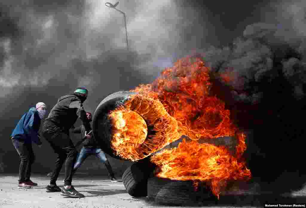 A Palestinian protester moves a burning tire during clashes with Israeli troops near the Jewish settlement of Beit El in the Israeli-occupied West Bank on March 27. (Reuters/Mohamad Torokman)