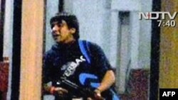 One of the Mumbai attackers carrying an automatic rifle as he enters a train station in Mumbai on November 26.
