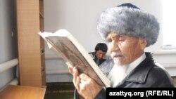 Местный житель читает Коран в мечети имени духовного наставника Досжана. Поселок Шубаркудык. 16 ноября 2013 года.