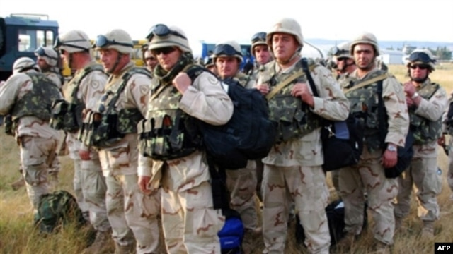 Georgian soldiers carry their gears upon their arrival from Iraq at Tbilisi airport in August 2008.
