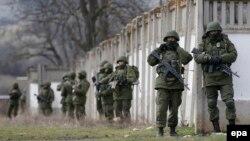 Вооруженные люди в военной форме без опознавательных знаков, заблокировавшие украинскую воинскую часть к Крыму в селе Перевальное недалеко от Симферополя. 19 марта 2014 года.