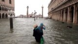 Italy -- A woman holds a child as she walks in a flooded Saint Mark Square during a period of seasonal high water in Venice, Italy October 29, 2018