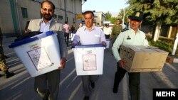 Мужчины с урнами для бланков голосования на президентских выборах в Иране. Тегеран, 14 июня 2013 года.