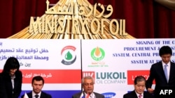 Iraqi Oil Minister Abdelkarim al-Luaybi (center) sits between LUKoil Mideast's chief, Iskander Nasyrov (left), and Samsung Vice President Park Ki-Seok (right) as they sign a $1 billion deal to develop Iraq's second-biggest oil field in Al-Basrah in March.
