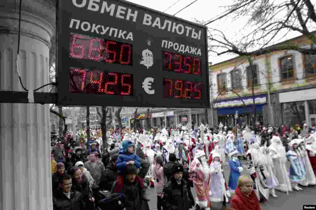 People dressed as Ded Moroz (Father Frost), his granddaughter Snegurochka, and other characters, walk during a festive preholiday procession, with a board showing currency exchange rates seen in the foreground, in Krasnodar, Russia, on December 20. (Reuters/Eduard Korniyenko)