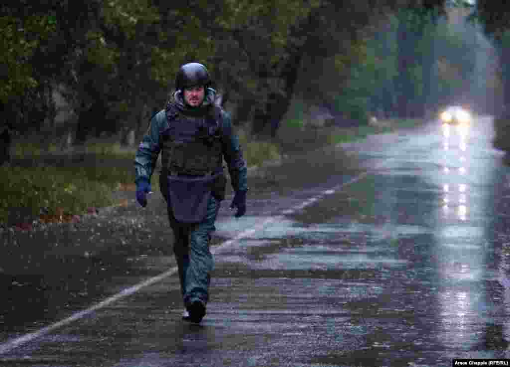 As rain and mortar shells fall, van Helten walks to the end of the road to check the painting.