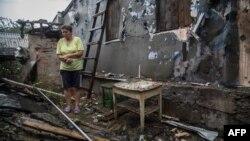 Жінка біля свого зруйнованого обстрілами будинку в Золотому, за 60 кілометрів на захід від Луганська, 16 серпня 2015 року
