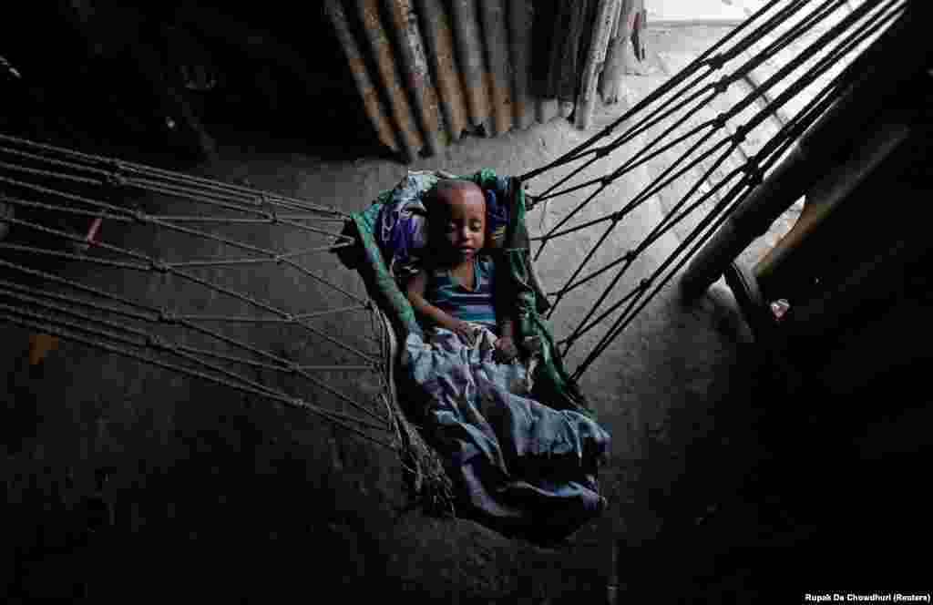 An infant sleeps in a hammock at a makeshift shelter in Kolkata on April 23. (Reuters/Rupak De Chowdhuri)