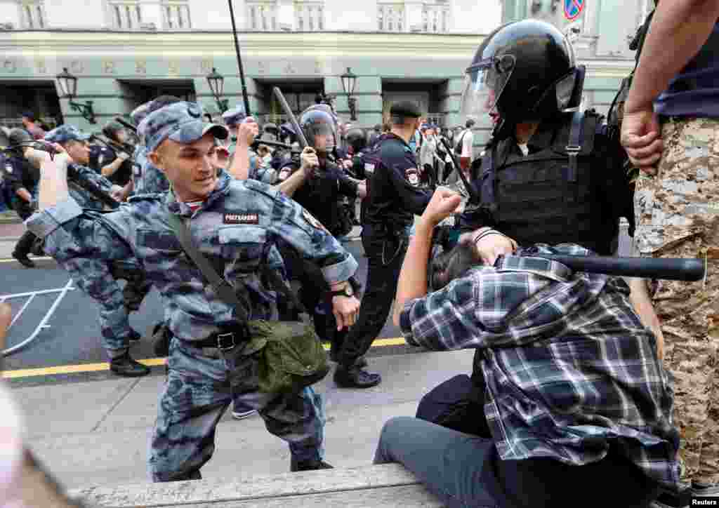 A Russian national guardsman beats a protester with a rubber baton during protests in Moscow. Video of the incident show the guardsman striking the detained man twice with full force, before a bystander punches the riot policeman on right.