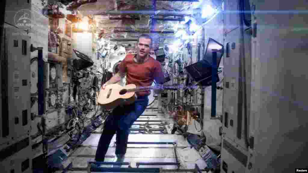 "Canadian astronaut and International Space Station (ISS) Commander Chris Hadfield performs his zero-gravity version of David Bowie's hit ""Space Oddity."" The video, with its familiar refrain of ""Ground control to Major Tom,"" has had millions of hits on YouTube and is being touted as the first music video ever filmed in space. Hadfield returned to Earth on May 14. (NASA via Reuters)"