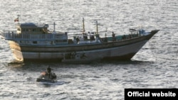 "A photo distributed by the U.S. Navy showing a safety boat from the ""USS Kidd"" observing the January 5 boarding of Iran-flagged fishing dhow ""Al Molai"" in Arabian Sea after a reported distress call saying the fishing vessel had been captured by pirates."