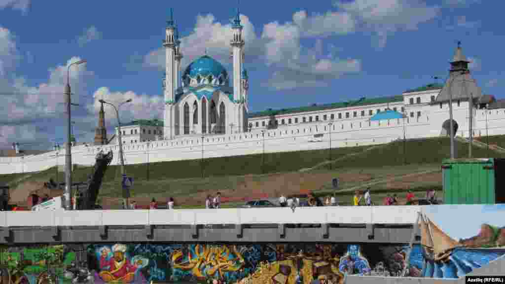 A mural lines the edges of a reservoir near a central mosque.