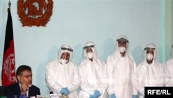 Afghan Health Minister Said Mohammad Amin Fatami speaks at a press conference on November 2 about swine flu. He is surrounded by doctors dressed in full protective suits from a Kabul lab designed to diagnose the H1N1 virus.