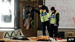Police forensics experts examine the remains of a suspected suicide bomber in Stockholm.
