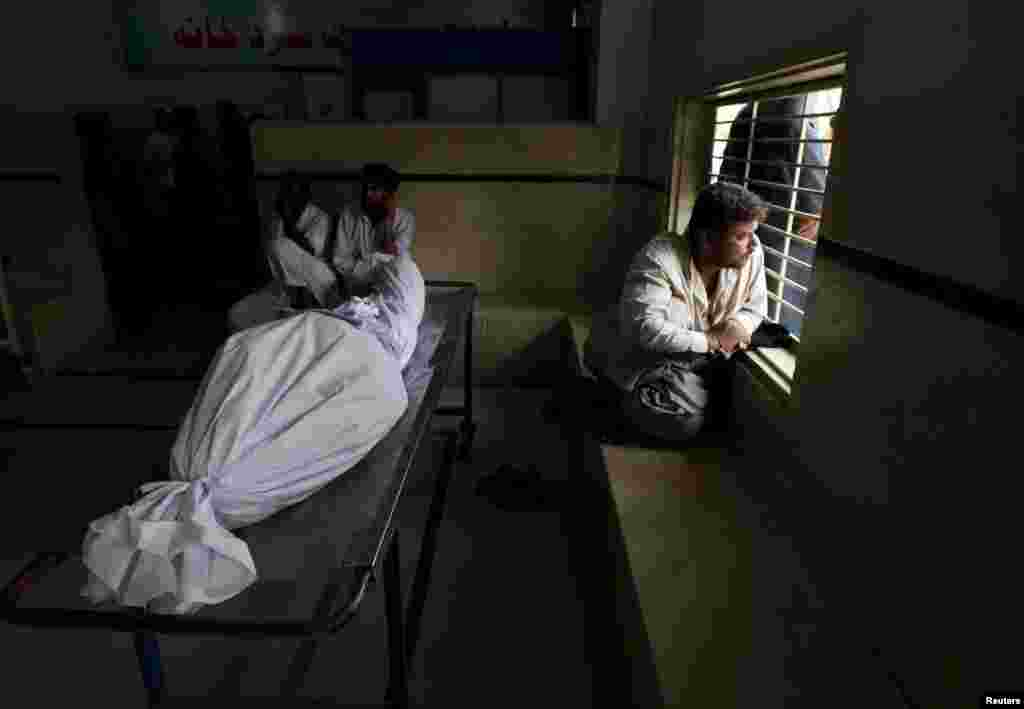 Karachi residents sit beside the body of a dead relative while waiting for an ambulance at a city morgue.