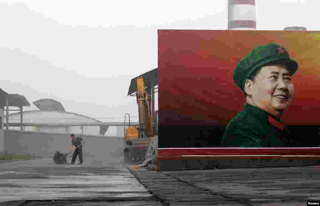 A worker cleans near a poster of the late Chairman Mao Zedong at a thermal power plant in Henan Province.