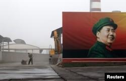 Рабочий подметает территорию у проходной завода в селе Наньжи провинции Хэнань. 25 сентября 2012 года.