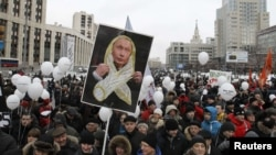 Demonstrators gathered holding placards and balloons during a December 24 protest in Moscow against the Duma elections earlier that month.