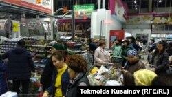 Алматыдағы азық-түлік сататын гипермаркеттердің бірінде кезекте тұрған жұрт. 12 наурыз 2020 жыл.