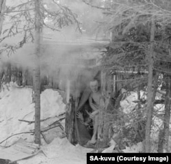 Finnish fighters peek out from a sauna during the war.