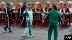 Turkmen President Gurbanguly Berdymukhammedov (center) waves to the media during the starting ceremony of a 500-day nationwide horse race at the historical site of Nisa just outside Ashgabat on May 5 in preparation for the 2017 Asian Indoor and Martial Arts Games.
