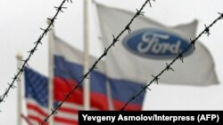 (Left to right:) The flags of the United States, Rusia and the Ford motor company fly behind barbed wire at an automobile plant in Vsevolozhsk. The automobile plant announced this week that it is closing three of its factories in Russia. (file photo)