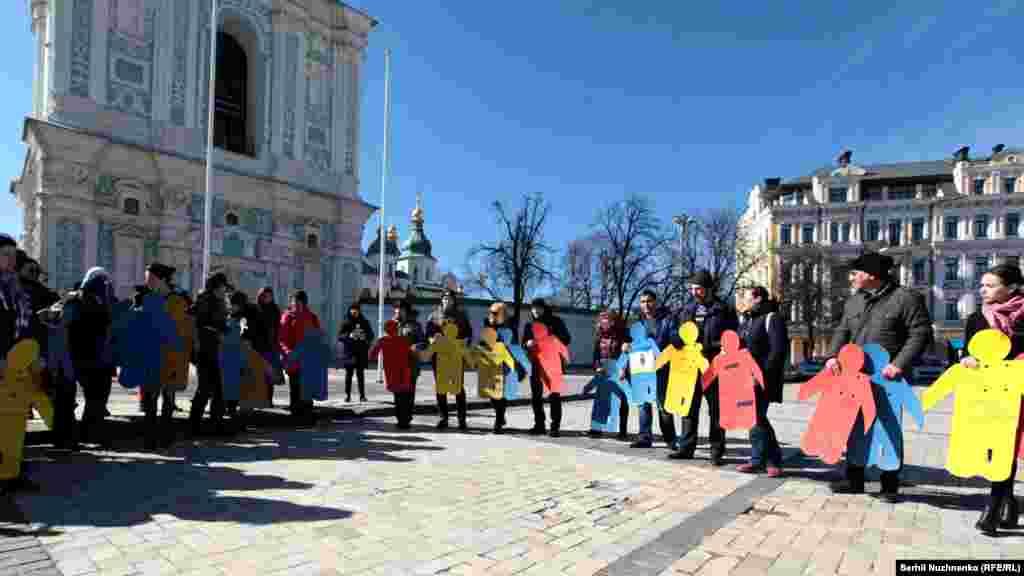 Активісти тримають у руках картонні людські фігури на пам'ять про Решата Аметова, кримськотатарські прапорці; деякі активісти тримали маленькі паперові фігури із заклеєним ротом, символізуючи порушення прав людини в анексованому Росією Криму