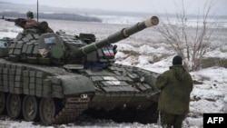 A pro-Russian separatist stands in front of a tank at a checkpoint in Yenakieve, 25 kilometers from the eastern town of Debaltseve, on January 29.