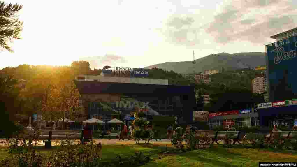 Заходящее за горы солнце окрашивает листву деревьев у кинотеатра «Планета Кино IMAX»