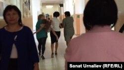 На заднем плане: сотрудники средней школы села Березовка Западно-Казахстанской области несут в медицинский пункт ученицу 6-го класса Любовь Воскобой, упавшую в обморок. 18 сентября 2015 года.