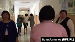 Kazakhstan – School employees carry student Lubov Voskoboy to the medical service after she collapsed. Berezovka, 18Sep2015