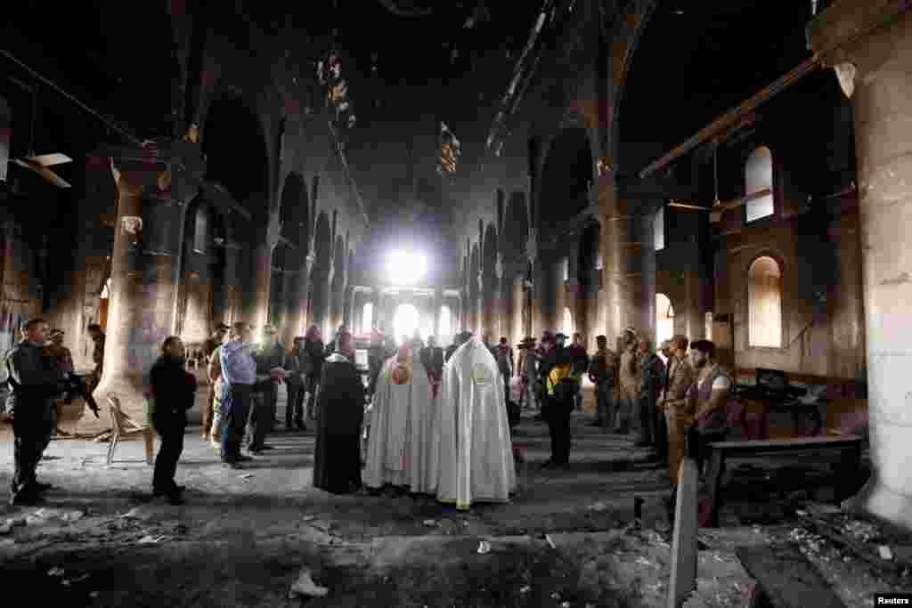 Iraqi priests hold the first Mass at the Grand Immaculate Church since it was recaptured from Islamic State militants in Qaraqosh, near Mosul, Iraq, on November 2. (Reuters/Alaa Al-Marjani)