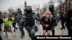 Служители на силите за сигурност задържат протестираща по време на демонстрациите в Русия