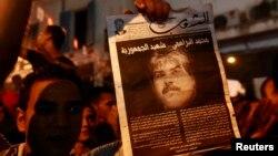 Демонстранти носат фотографија на убиениот опозициски политичар Мухамад Брахми.
