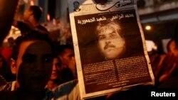 Демонстрант несет постер с портретом убитого тунисского оппозиционного политика Мохаммеда Брахми. 25 июля 2013 года.